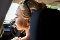 Happy teenage girl or young woman in car Royalty Free Stock Photo
