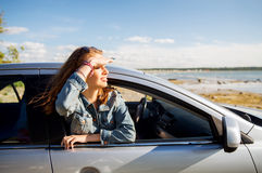 Happy teenage girl or young woman in car. Summer vacation, holidays, travel, road trip and people concept - happy smiling teenage girl or young woman in car at Stock Photography