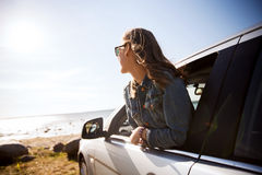 Happy teenage girl or young woman in car. Summer vacation, holidays, travel, road trip and people concept - happy smiling teenage girl or young woman in car at Stock Images