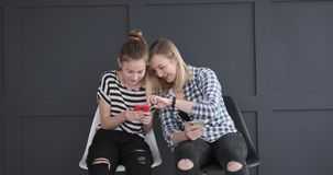 Teen girls discussing while using social media app on mobile phones stock video