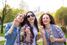 Happy teenage girls hawing fun spend time together in the city park Stock Images