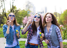 Happy teenage girls hawing fun spend time together in the city park.  Royalty Free Stock Photography
