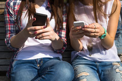Happy teenage girls texting sms hawing fun spend time together in the city park Stock Photography
