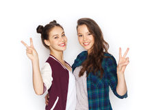 Happy teenage girls hugging and showing peace sign Stock Images