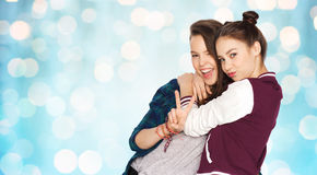 Happy teenage girls hugging and showing peace sign Royalty Free Stock Image