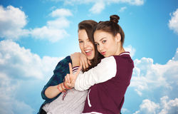 Happy teenage girls hugging and showing peace sign Stock Image