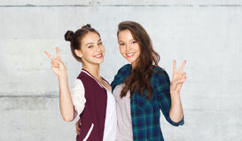 Happy teenage girls hugging and showing peace sign Royalty Free Stock Images