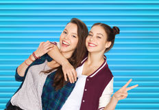 Happy teenage girls hugging and showing peace sign. People, teens and friendship concept - happy smiling pretty teenage girls or friends hugging and showing Stock Image