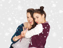 Happy teenage girls hugging and showing peace sign Stock Photo