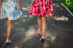 Happy Teenage girls in light dresses walking on sun light, outdoors. Unrecognizable girlfriends having fun together Stock Photography