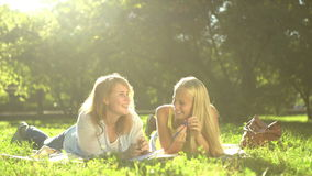 Happy Teenage girls reading a book outdoors. Teenage girlfriends having fun and laughing. 4k stock video footage