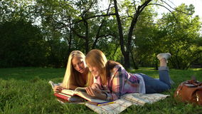 Happy Teenage girls reading a book outdoors. Teenage girlfriends having fun and laughing. Slow motion video footage 1080 full hd. High speed camera shot stock video