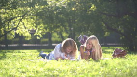 Happy Teenage girls reading a book outdoors. Happy Teenage girls reading a book on green meadow in a city park. Teenage girlfriends having fun and laughing. 4k stock footage