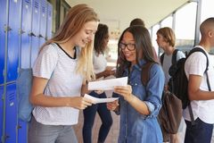 Happy teenage girls sharing exam results in school corridor Royalty Free Stock Photo