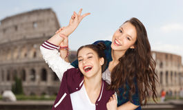 Happy teenage girls showing peace over coliseum Stock Image