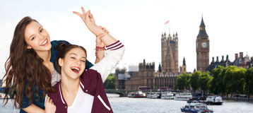 Happy teenage girls showing peace sign in london. People, travel, tourism and friendship concept - happy smiling pretty teenage girls showing peace hand sign Stock Photo