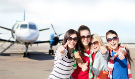Happy teenage girls showing thumbs up at airport. Summer holidays, vacation, travel and people concept - happy teenage girls in sunglasses or young students Royalty Free Stock Photo