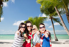 Happy teenage girls showing thumbs up on beach Stock Photos