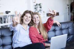 Two gorgeous brunette woman looking at camera with smile and showing peace sign with fingers stock photos