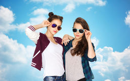 Happy teenage girls in sunglasses over blue sky Stock Photo