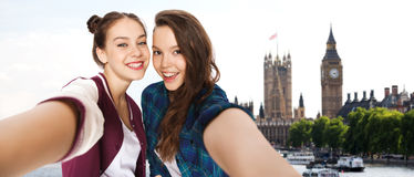 Happy teenage girls taking selfie in london. People, travel, tourism and friendship concept - happy smiling pretty teenage girls taking selfie over london Stock Photo