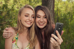 Happy teenage girls taking selfshot or selfy picture of themselv Stock Photo