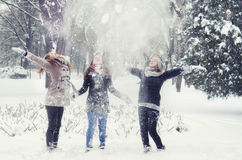 Happy teenage girls throwing snow in the air Stock Photo