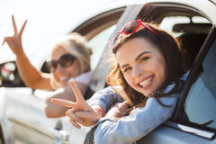 Happy teenage girls or women in car at seaside Royalty Free Stock Image