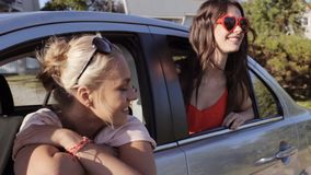 Happy teenage girls or women in car at seaside 67. Summer vacation, holidays, travel, road trip and people concept - happy teenage girls or young women in car at stock footage