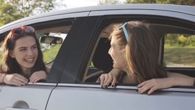 Happy teenage girls or women in car at seaside 61. Summer vacation, holidays, travel, road trip and people concept - happy teenage girls or young women in car at stock video