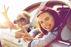 Happy teenage girls or women in car at seaside. Summer vacation, holidays, travel, road trip and people concept - happy teenage girls or young women in car at Stock Images