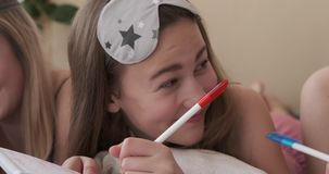 Teen girls writing shopping list together on notepad stock video footage