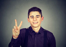 Happy teenage guy showing victory or peace sign Royalty Free Stock Images