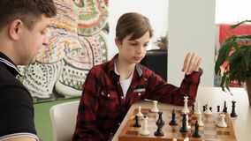 Happy teenage kid is laughing winning his father in chess front view slow motion