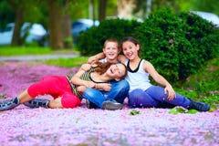 Happy teenage kids having fun in spring park. Happy kids, teenagers having fun in blooming park, spring outdoors Royalty Free Stock Photo