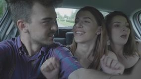 Happy teenage man taking selfie video streaming with couple dancing funny crazy girls while they going on summer holiday party. And fun roadtrip concept stock footage
