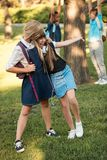 Schoolgirls with backpacks in park. Happy teenage schoolgirls with backpacks standing embracing in park Royalty Free Stock Photo