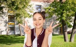 Happy teenage student girl showing peace sign Royalty Free Stock Photos