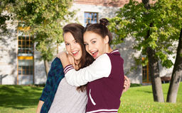 Happy teenage student girls hugging over campus Royalty Free Stock Photo