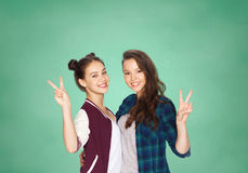 Happy teenage student girls showing peace sign Stock Image