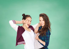 Happy teenage student girls showing peace sign Royalty Free Stock Images