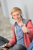 Happy teenage student thumb-up listen to music Stock Image
