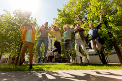 Happy teenage students or friends jumping outdoors Stock Images