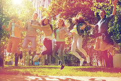 Happy teenage students or friends jumping outdoors Royalty Free Stock Image