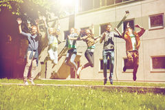Happy teenage students or friends jumping outdoors Royalty Free Stock Photo