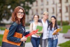 Happy teenage students with school folders Stock Photos
