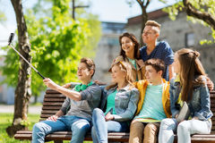 Happy teenage students taking selfie by smartphone Stock Photos
