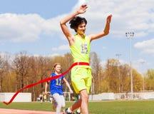 Happy teenage winner crossing the finish line Royalty Free Stock Photo