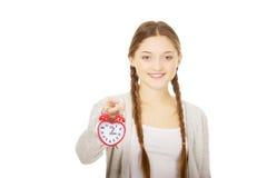 Happy teenage woman with alarmclock. Royalty Free Stock Image