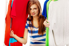 Happy teenage woman between clothes on hanger Royalty Free Stock Images